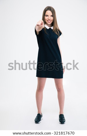 Full length portrait of a smiling woman pointing finger at camera isolated on a white background - stock photo
