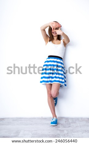 Full length portrait of a smiling woman showing frame gesture - stock photo