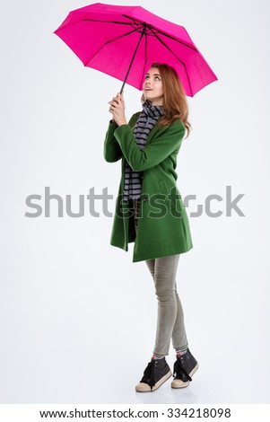 Full length portrait of a smiling woman standing with pink umbrella and looking up isolated on a white background - stock photo