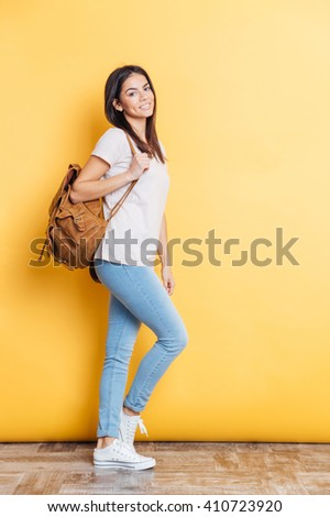 Full length portrait of a smiling woman with backpack standing on yellow background and looking at camera - stock photo