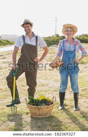 Full length portrait of a smiling young couple with vegetables standing in the field