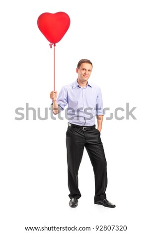 Full length portrait of a smiling young man holding a red heart shaped balloon isolated on white background