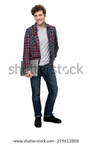 Full length portrait of a smiling young man standing with laptop - stock photo