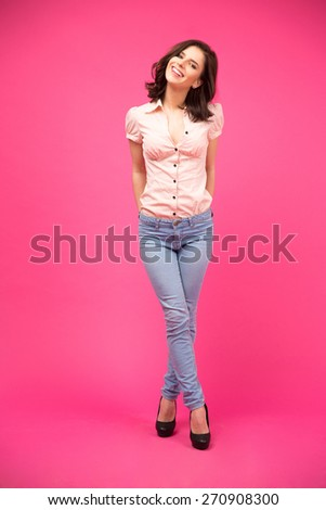 Full length portrait of a smiling young woman standing over pink background and looking at camera - stock photo