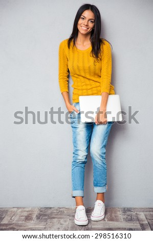 Full length portrait of a smiling young woman standing with laptop on gray background. Looking at camera - stock photo