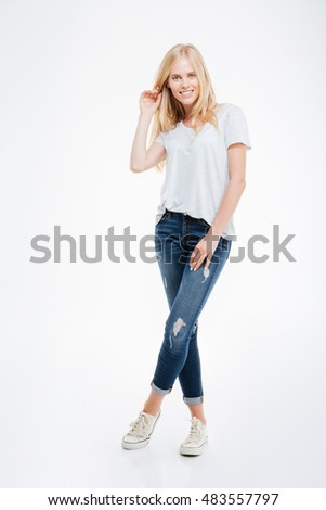 Full length portrait of a smiling young woman standing with legs crossed isolated on a white background