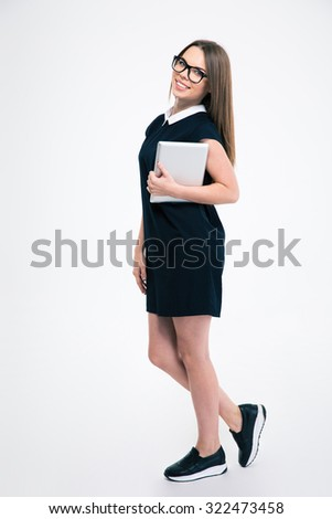 Full length portrait of a smiling young woman standing with tablet computer isolated on a white background - stock photo