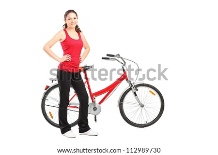 Full length portrait of a sporty girl posing next to a bike isolated on white background - stock photo