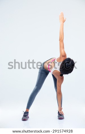 Full length portrait of a sporty woman stretching over gray background - stock photo