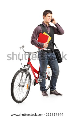 Full length portrait of a student talking on phone and standing by a bike isolated on white background - stock photo