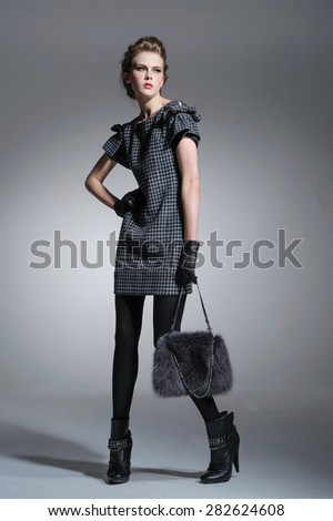 full-length Portrait of a styled professional model posing in studio  - stock photo
