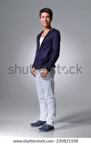 Full length portrait of a stylish young man standing with hands in pockets on light  background - stock photo