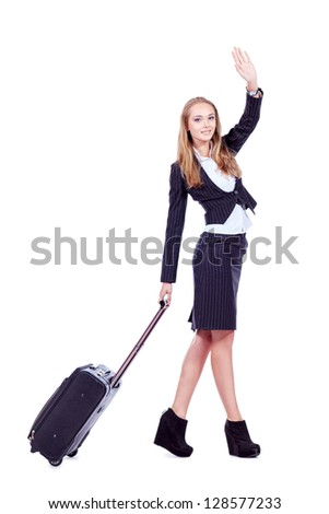 Full length portrait of a successful young business woman standing with travel bag. Isolated over white.