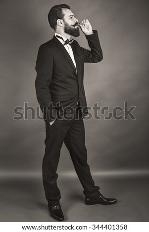 Full length portrait of a successful young man with retro look smoking a cigar over gray background - stock photo