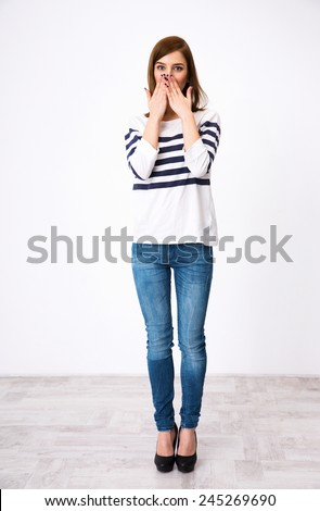 Full length portrait of a surprised woman covering her mouth - stock photo