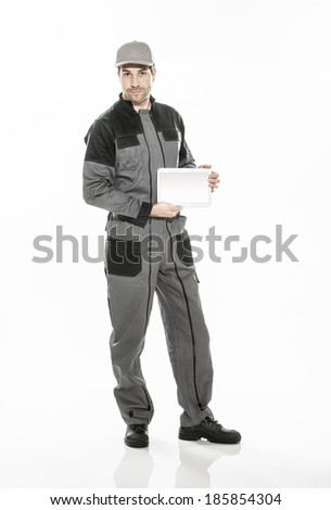 Full length portrait of a technician in a uniform showing a digital tablet - stock photo