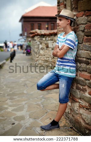 Full length portrait of a teenage boy in an old town  - stock photo
