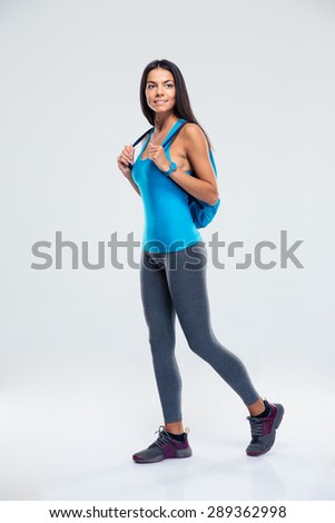 Full length portrait of a thoughtful sporty woman with backpack over gray background. Looking away - stock photo