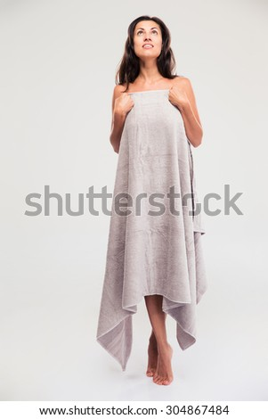 Full length portrait of a thoughtful woman standing in towel isolated on a white background. Looking up