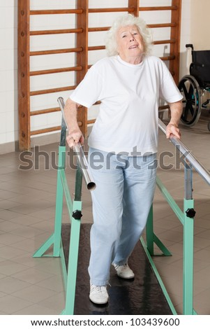 Full length portrait of a tired senior woman on walking track at hospital gym - stock photo