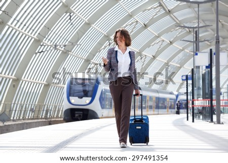 Full length portrait of a traveling business woman walking with bag and phone - stock photo