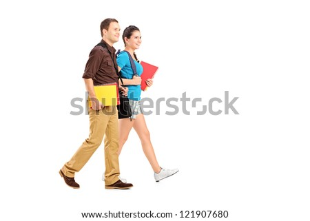 Full length portrait of a two students holding books and walking isolated on white background - stock photo