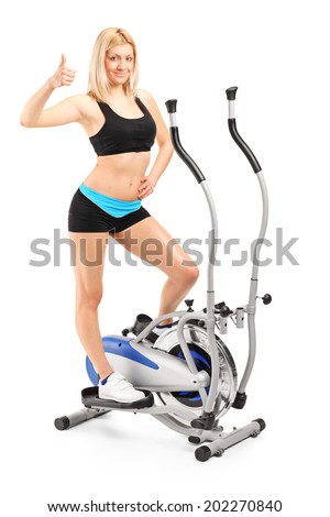 Full length portrait of a woman giving a thumb up on a cross trainer machine isolated on white background