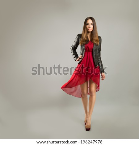 Full Length Portrait of a Woman in Red Chiffon Dress on Gray Backgound