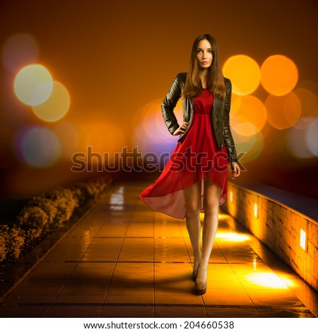 Full Length Portrait of a Woman in Red Chiffon Dress Walking in Night City. Modern Nighlife Concept. Bokeh Background. Copy Space. - stock photo