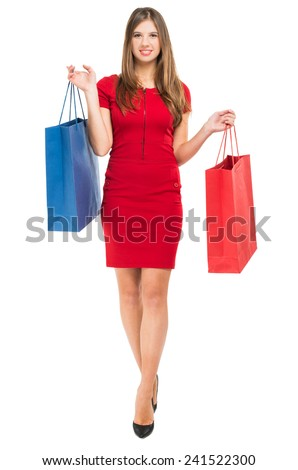 Full length portrait of a woman in red dress holding shopping bags - stock photo
