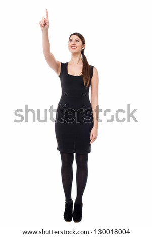 Full length portrait of a woman pointing at something specific.