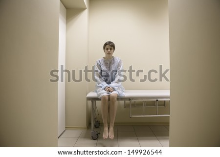 Full length portrait of a woman waiting for medical examination - stock photo