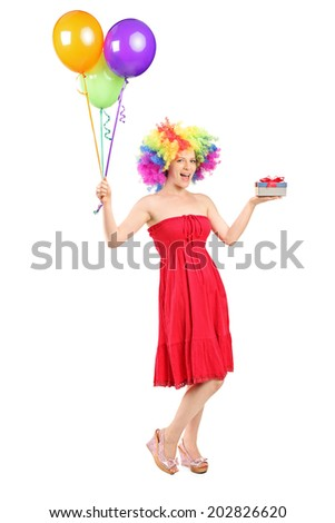 Full length portrait of a woman wearing a wig and holding a present and a bunch of balloons isolated on white background - stock photo