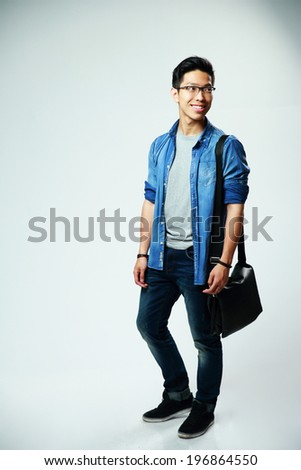 Full length portrait of a young asian man on gray background - stock photo