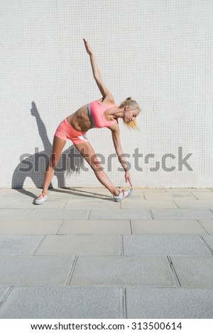 Full length portrait of a young athletic female with slender body do physical exercises outdoors in sunny summer day,beautiful woman dressed in tracksuit doing fitness training in urban setting  - stock photo