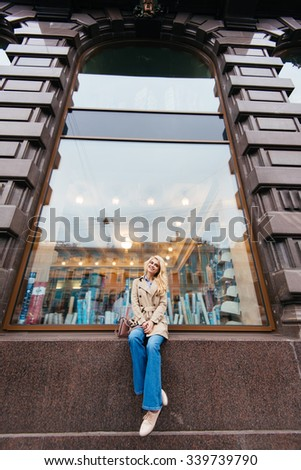 Full length portrait of a young attractive woman with beautiful smile posing while sitting on a shop sill against big window, charming female enjoying rest after walking in the fresh air in autumn day - stock photo