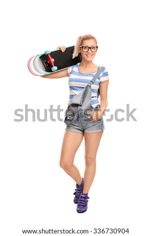 Full length portrait of a young blond hipster girl carrying a skateboard over her shoulder and looking at the camera isolated on white background - stock photo