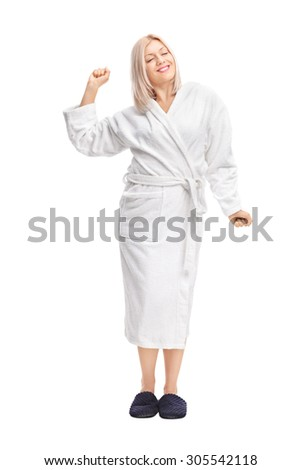 Full length portrait of a young blond woman in a white bathrobe stretching herself isolated on white background - stock photo