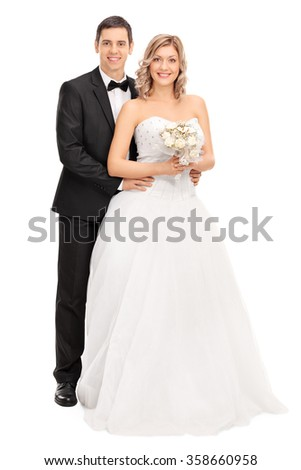 Full length portrait of a young bride and groom posing together isolated on white background - stock photo