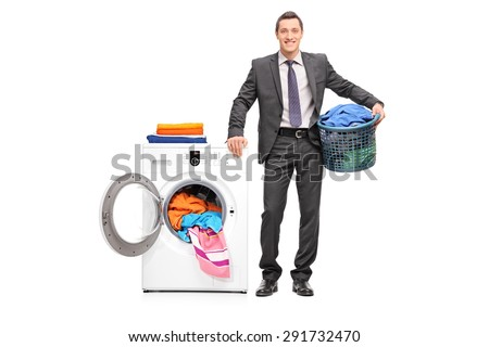 Full length portrait of a young businessman holding a laundry basket and posing next to a washing machine isolated on white background - stock photo