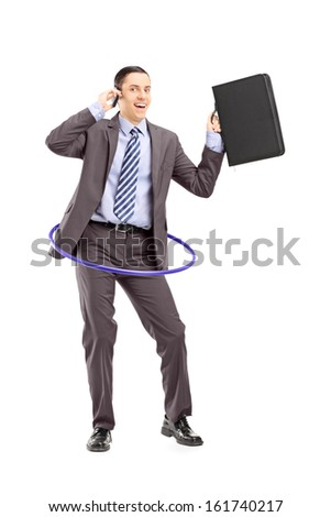 Full length portrait of a young businessman in suit dancing with a hula hoop and talking on a mobile phone isolated on white background