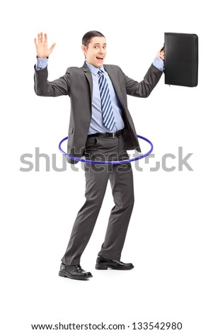 Full length portrait of a young businessman in suit holding a briefcase and dancing with a hula hoop isolated on white background