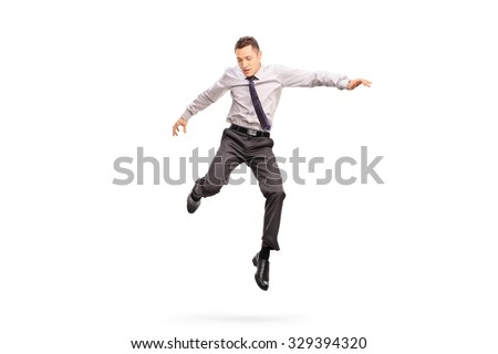 Full length portrait of a young businessman jumping in the air and looking down isolated on white background - stock photo