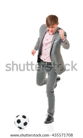 Full length portrait of a young businessman manager kicking a soccer ball, isolated on white background