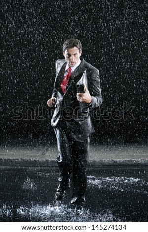 Full length portrait of a young businessman with binder running in rain - stock photo