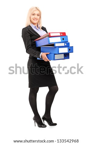 Full length portrait of a young businesswoman carrying folders isolated on white background - stock photo