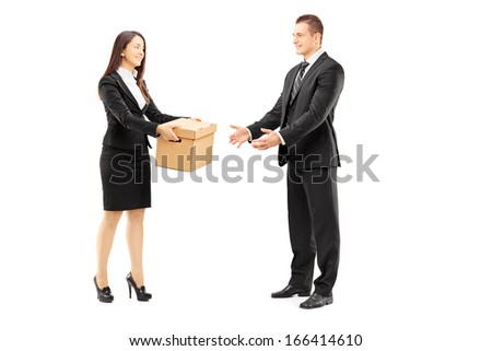 Full length portrait of a young businesswoman giving a box to her male colleague, isolated on white background - stock photo