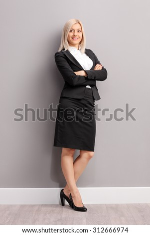 Full length portrait of a young businesswoman in black suit leaning against a gray wall and looking at the camera - stock photo