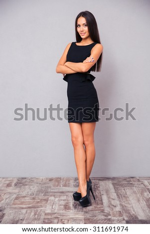 Full length portrait of a young businesswoman standing with arms folded on gray background - stock photo