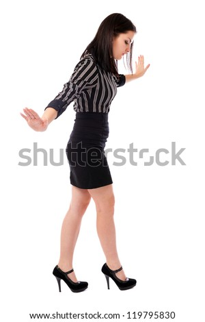 Full length portrait of a young businesswoman walking on imaginary rope
